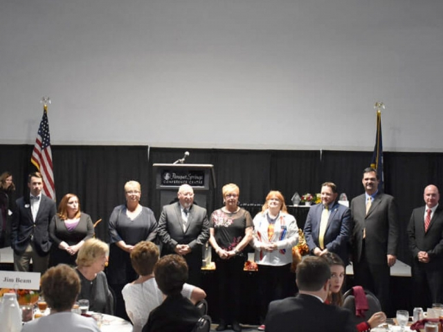 Bullitt County Chamber of Commerce Board of Directors stand in front of the room at the 2018 Annual Awards Dinner