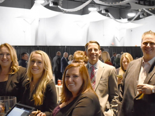 Bullitt County Chamber of Commerce Annual Dinner attendees standing at bar, smiling at camera