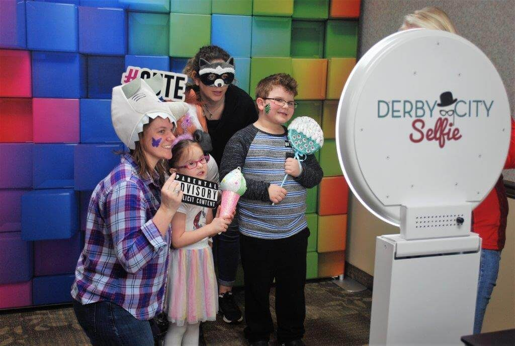 2019 KidsFest - A family poses with props in the Derby City Selfie photo booth