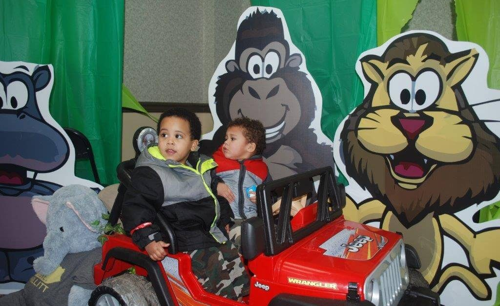 2019 KidsFest - Children sit in a Jeep power wheel vehicle in front of smiling lion, gorilla and hippo cardboard cutouts