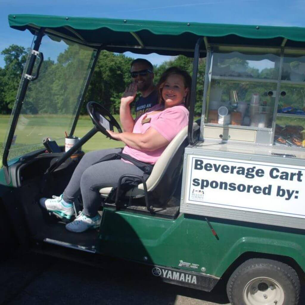 Two people smiling and waving from the beverage cart