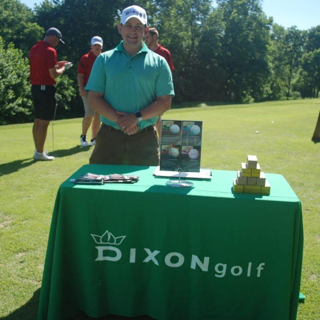 A representative from Dixon Golf stands smiling at their table on the green