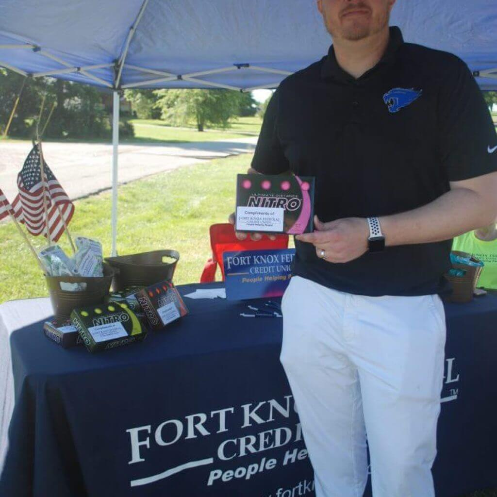 A representative with Ft. Knox Credit Union poses by their table on the green
