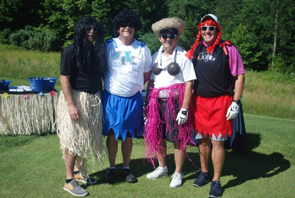 """A group of men pose in grass skirts and wigs at the """"skirt hole"""""""