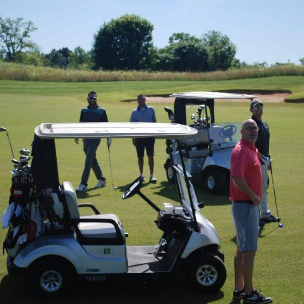A golf team stands by their carts while in the middle of collecting their golf balls from the green