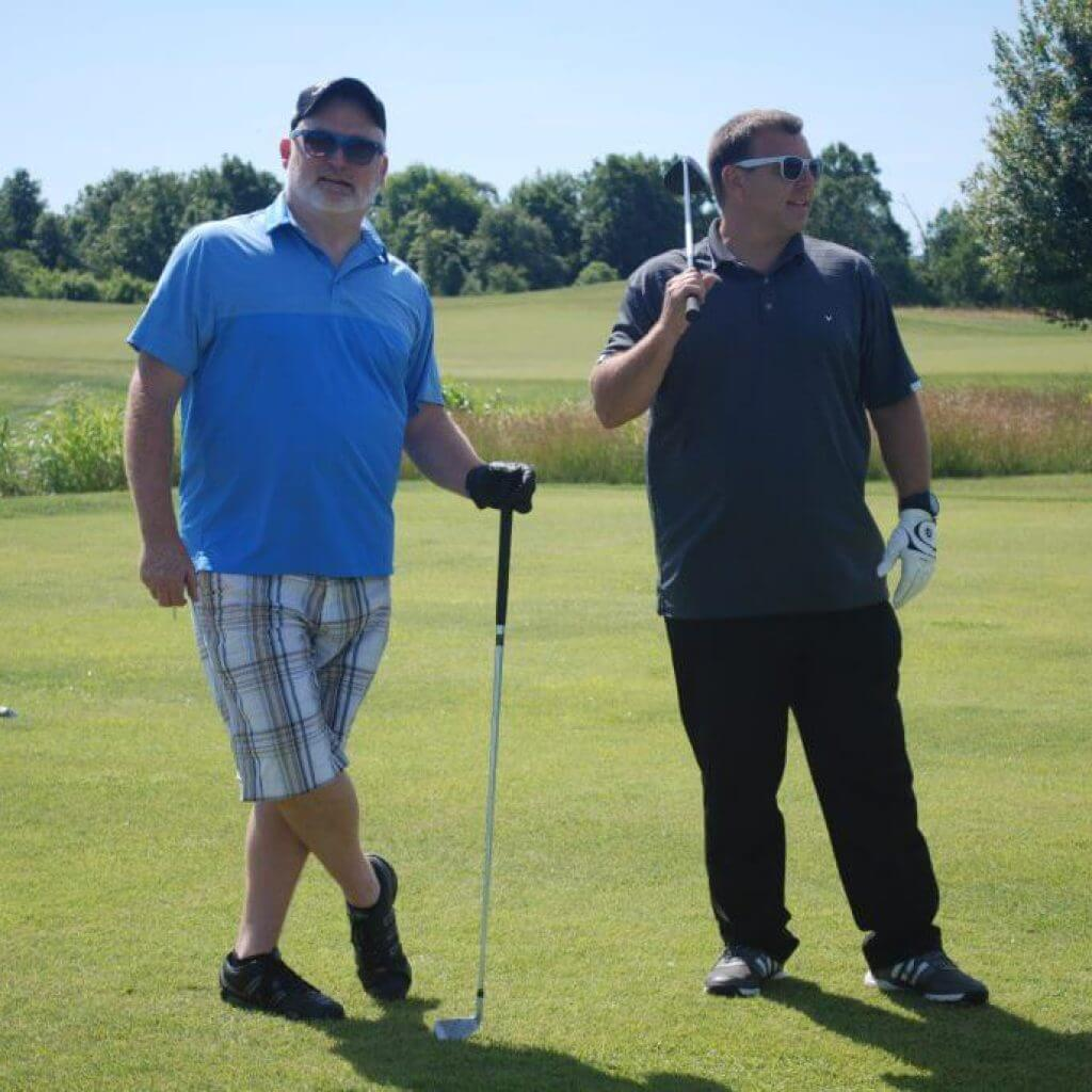 Two golfers pose while holding their clubs on the green