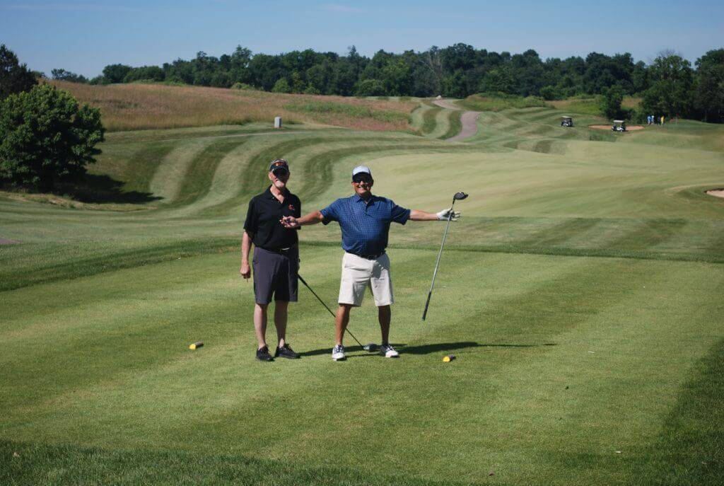 Two golfers pose on the green, one smiling with his arms outstretched and holding a golf club and cigar