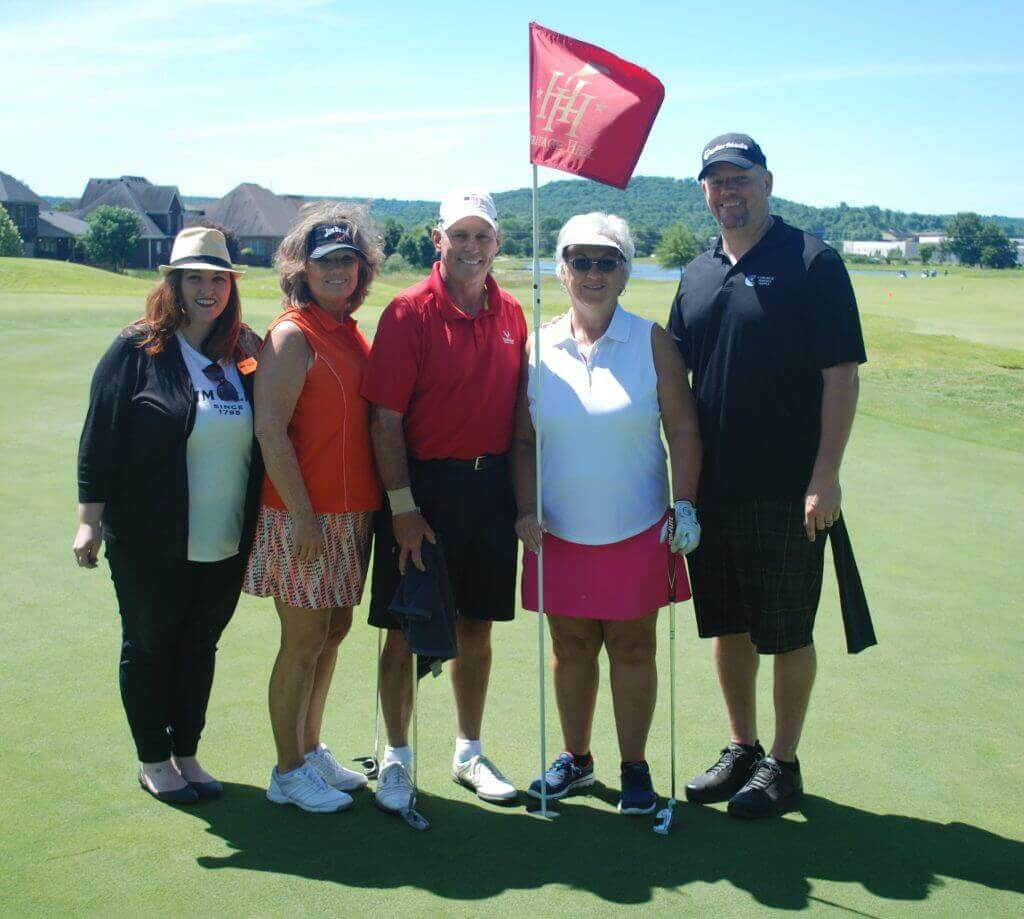 Jim Beam's first team of golfers posing by the flag on a hole