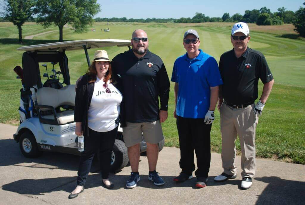 Jim Beam's second team of golfers posing by their golf cart on the cart path