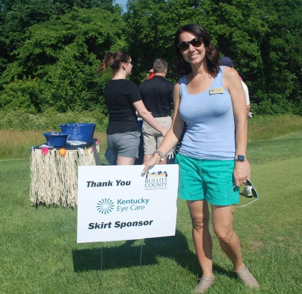 A representative with Kentucky Eye Care smiles beside their sponsorship sign