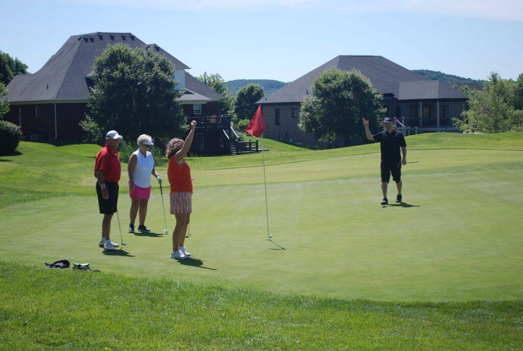 A team of golfers stands by the hole, one member with her arm in the air to celebrate a successful putt