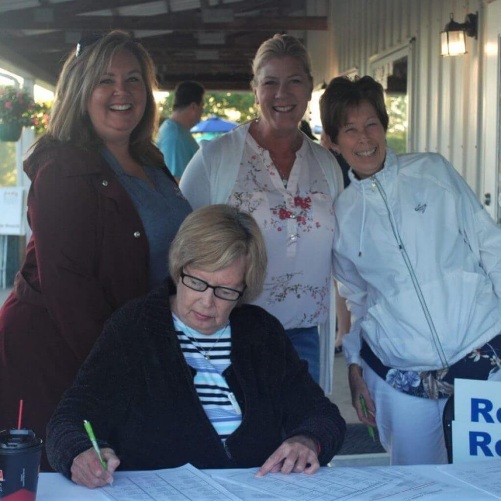 A group of 4 women smiling by the registration table