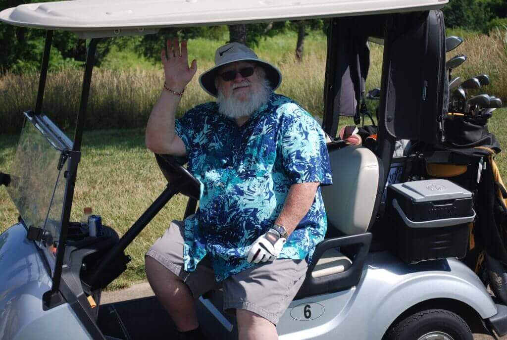 A golfer with a full, white beard smiles and waves from his golf cart