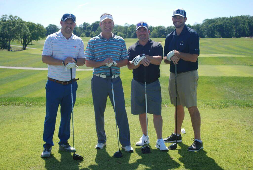The Rogers Group team poses with their hands balanced on the top of their golf clubs