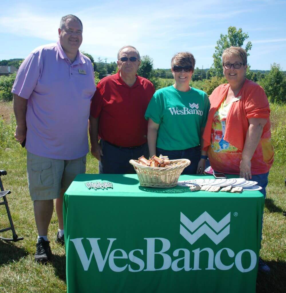 A group of 4 people from WesBanco smile beside their sponsor table
