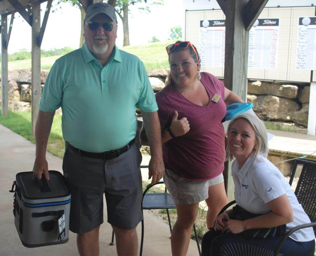 Bill Laird holds a Yedi cooler that he won as a door prize while standing beside Jamie Hampton and Mandey Lee